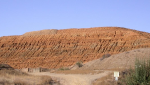 A mine tailings pile (which looks like a large pile of desert) against a blue sky.