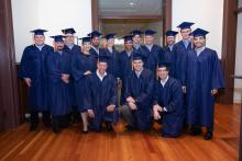 A group of people wearing blue graduation caps and gowns smiles for a photo.
