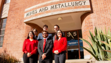 Mining students standing in front of the department building