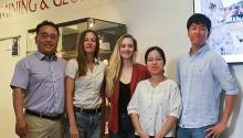 Associate professor Jaeheon Lee stands with four graduate students in a classroom.