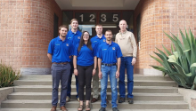 Five students wearing blue polos stand with Professor Brad Ross on the front steps of the mining engineering building.