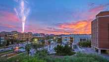 a photo of the busy University of Arizona mall at sunset, with a firework going off in the background on the left side.