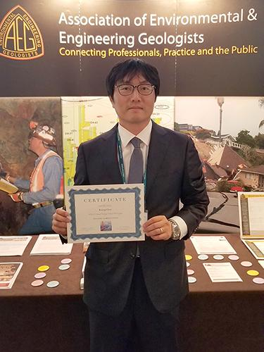"A man standing before a table and a banner reading ""Association of Environmental and Engineering Geologists; Connecting Professionals, Practice and the Public"" while holding up a certificate."