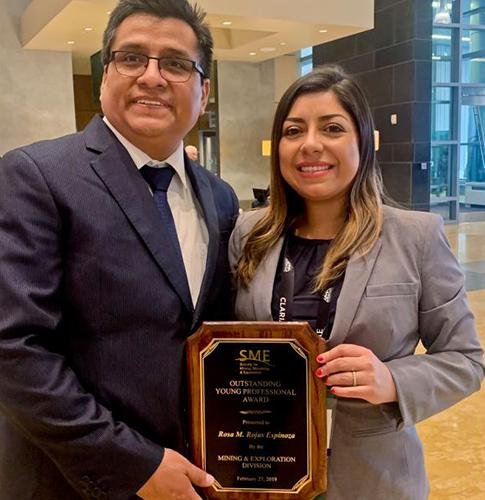 A woman and a man both holding a plaque naming Rosa Maria Rojas the SME Outstanding Young Professional for 2019