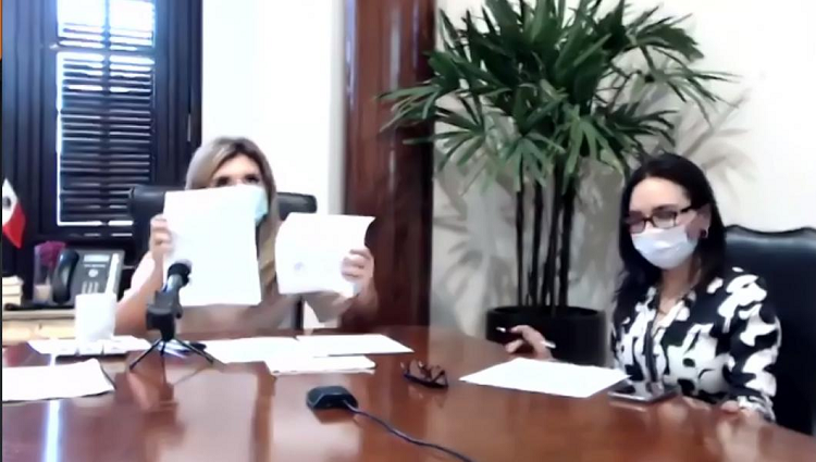 Blurry screencap of a Zoom meeting, in which two women wearing masks sit at a large table.
