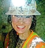 Alyssa Hom in hardhat and safety vest, covered in mud