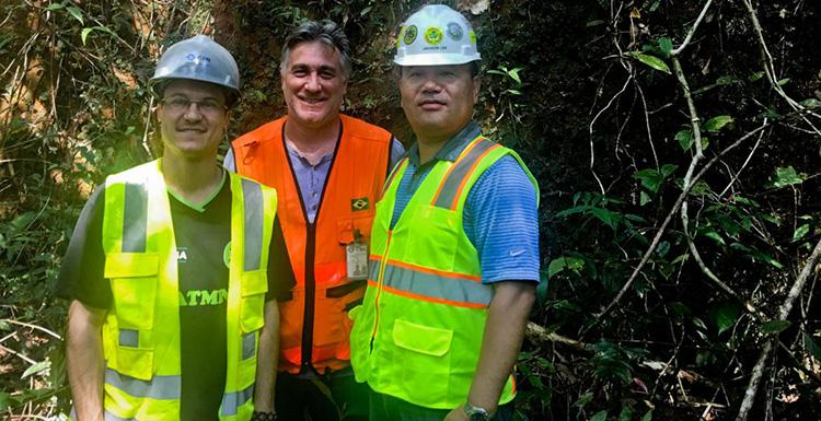 Jaeheon Lee in hard hat and reflective safety vest at a CSN Mining site in Brazil with site geologists Moises Avila and Roberto Virga.