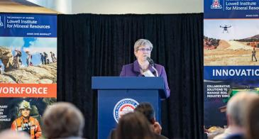 Mary Poulton stands behind a blue podium with the red-and-blue University of Arizona seal on it. She is flanked on either side by large posters touting the Lowell Institute's strengths in workforce development and innovation.